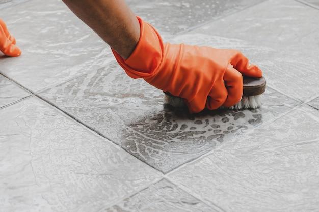 La mano del hombre que lleva guantes de goma naranja se usa para convertir la limpieza de fregado en el suelo de baldosas.
