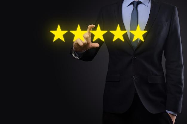 Mano del hombre que muestra una calificación excelente de cinco estrellas. señalando el símbolo de cinco estrellas para aumentar la calificación de la empresa. revisar, aumentar la calificación o clasificación, la evaluación y el concepto de clasificación.