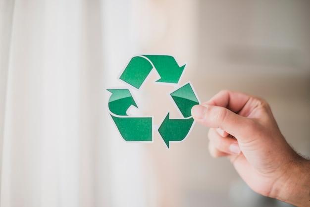 La mano del hombre que muestra el icono de reciclaje