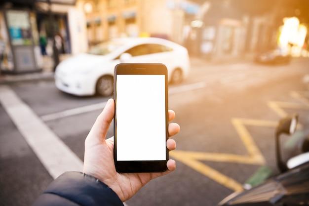 La mano del hombre que muestra el teléfono móvil con pantalla en blanco en la carretera