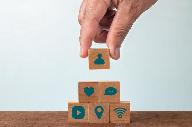 Mano del hombre que pone el bloque de cubo de madera con los medios sociales en la mesa de madera. concepto de redes sociales