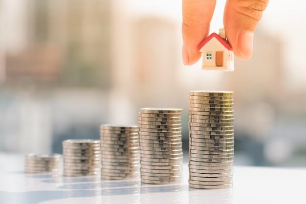 La mano del hombre que pone el modelo de la casa encima de pila de las monedas.