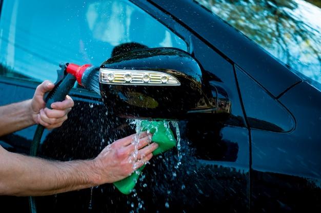 La mano del hombre que pule el auto negro con una esponja y otra mano sostiene la manguera para lavar al aire libre.