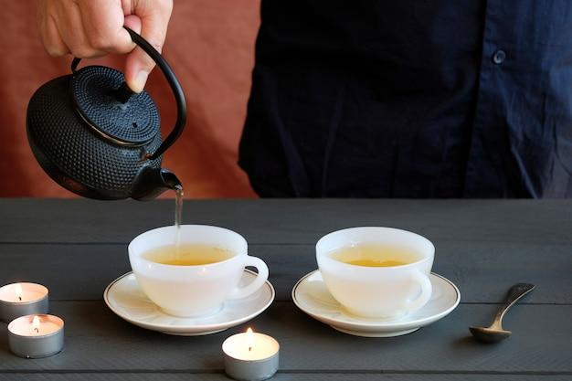 La mano del hombre que sirve dos tazas de té verde