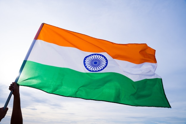 Mano del hombre que sostiene la bandera de la india en el fondo del cielo azul.