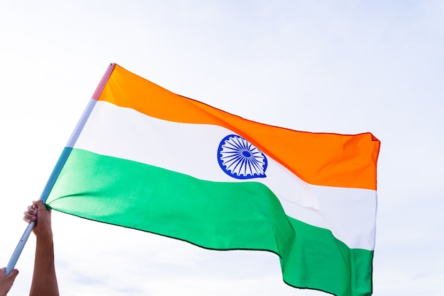 Mano del hombre que sostiene la bandera de la india en el fondo del cielo azul