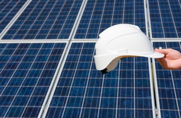 La mano del hombre que sostiene el barril protector blanco, cierre de la mano, fondo del campo del panel solar.