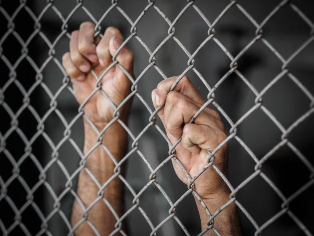 Mano del hombre que sostiene la cerca del acoplamiento de cadena para recordar el concepto del día de los derechos humanos