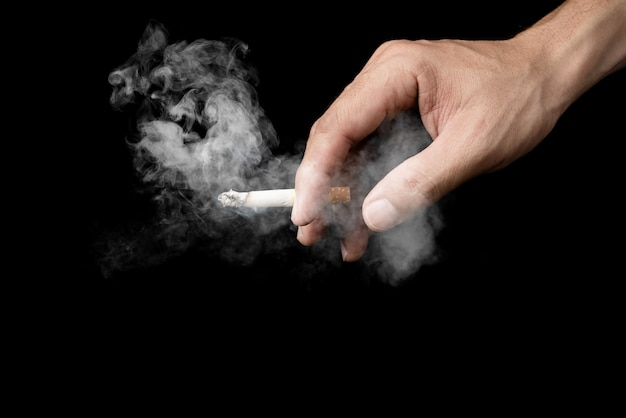 Mano del hombre que sostiene el fumar del cigarrillo en la oscuridad aislada en fondo negro