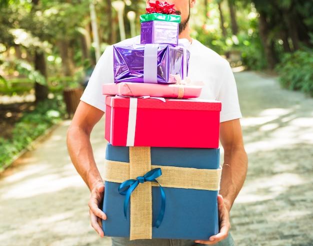 La mano del hombre que sostiene la pila de regalos multicolores