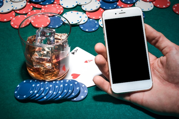 Mano del hombre que sostiene el teléfono móvil sobre la mesa de póquer con vaso de whisky