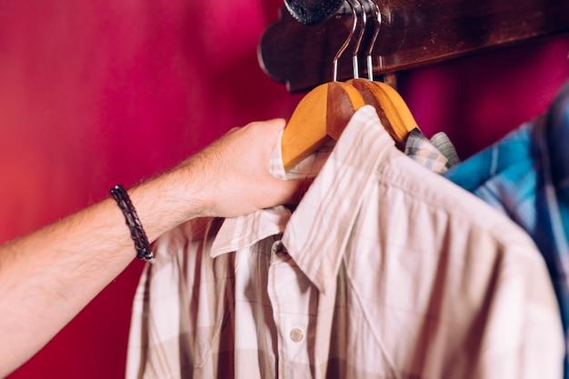 La mano del hombre que toma la camisa de la percha del gancho del estante en la pared roja