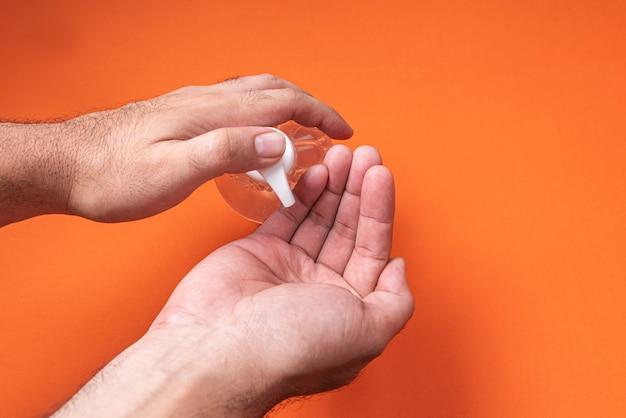 La mano del hombre en un recipiente con gel de alcohol en la pared de naranja