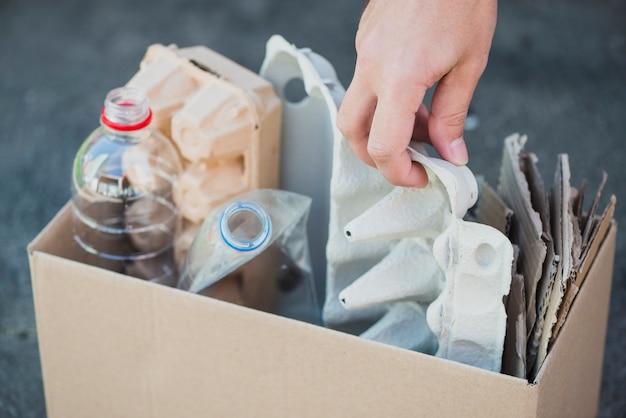 La mano del hombre recolecta botellas de plástico y cartón de huevos en la caja de reciclaje