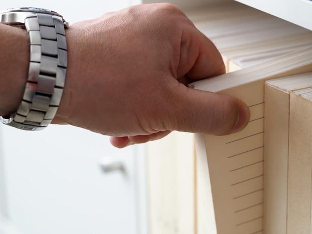 La mano del hombre en el reloj saca papel del archivo de la pila. proceso de optimización de paquetes de adquisición. imprime formularios de valores dentro de las hojas de esta serie. formularios de solicitud en oficina. método de procesamiento de hoja