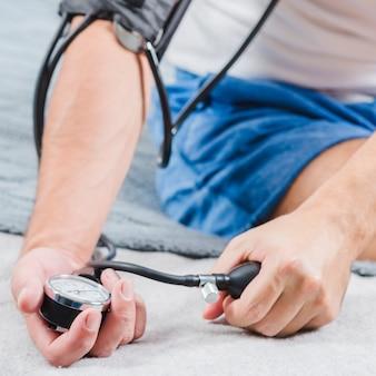 La mano de un hombre revisando su presión sanguínea.
