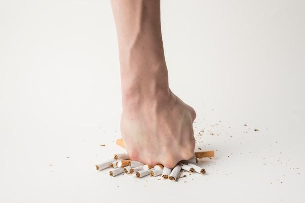 Mano del hombre rompiendo cigarrillos con su puño en superficie blanca