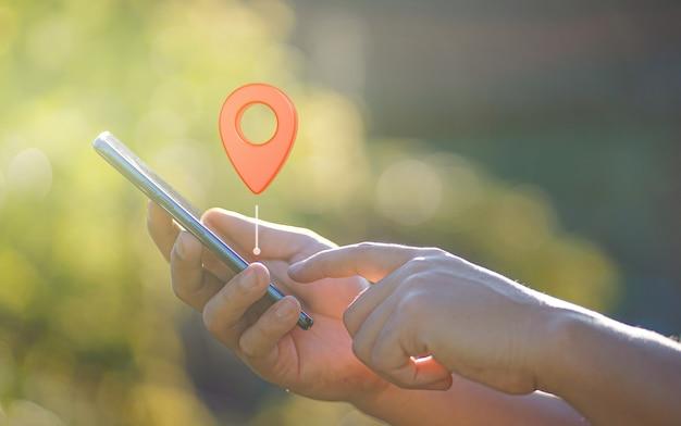 Mano de hombre con smartphone con icono de navegador gps de punto rojo pin