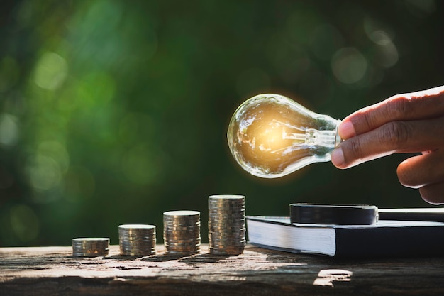 Mano de hombre sosteniendo una bombilla con pila de monedas y copia espacio para contabilidad, ideas y concepto creativo.