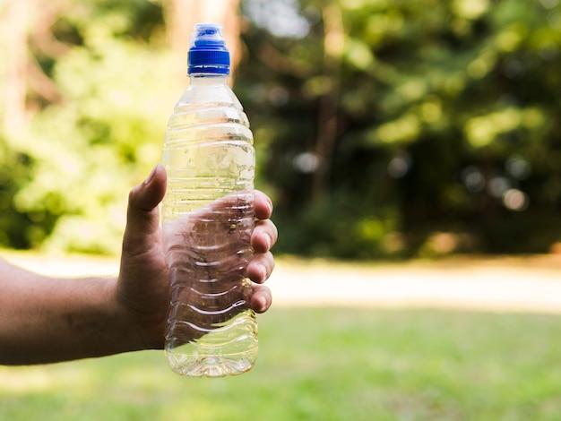 La mano del hombre sosteniendo la botella de agua plástica vacía al aire libre