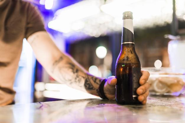La mano del hombre sosteniendo la botella de alcohol en la barra de bar