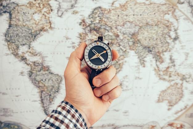 Mano de hombre sosteniendo brújula vintage con mapa del mundo como fondo