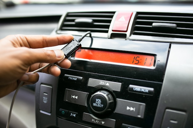 Mano de hombre sosteniendo cargar el teléfono inteligente móvil de batería usb en el coche.