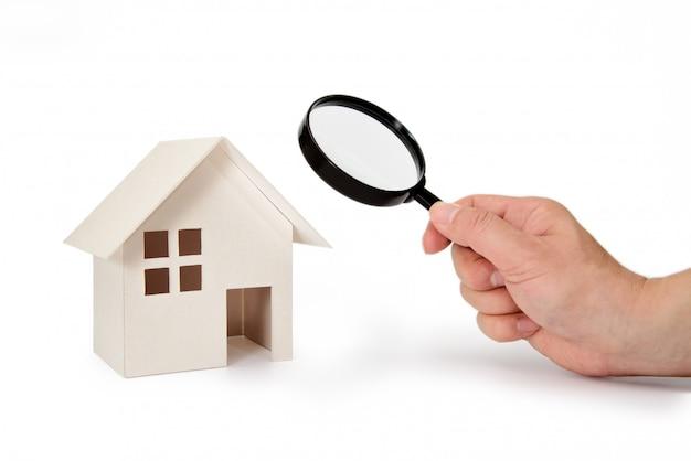 La mano del hombre sosteniendo una casa modelo y una lupa.