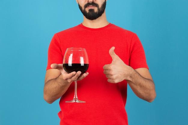 Mano de hombre sosteniendo una copa de vino tinto y mostrando el pulgar hacia arriba.