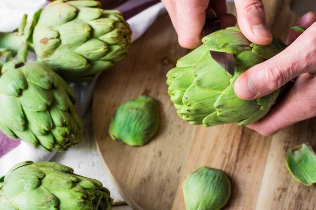 Mano del hombre sosteniendo el cuchillo y pelando alcachofas frescas, preparándose para cocinar, tabla de cortar