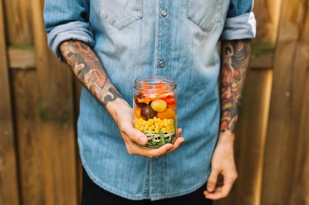 Mano del hombre sosteniendo el frasco abierto con ensalada de pasta