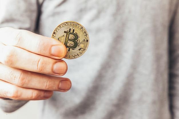 Mano de hombre sosteniendo la moneda bitcoin de oro criptomoneda
