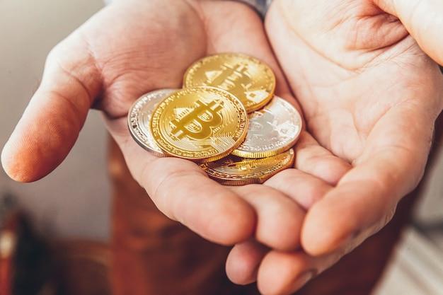 Mano de hombre sosteniendo la moneda bitcoin de oro y plata de criptomoneda