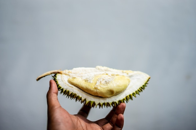 Mano de hombre sosteniendo la pieza de fruta durian