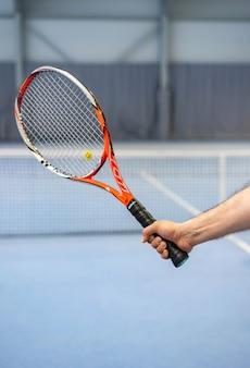 La mano del hombre sosteniendo la raqueta de tenis en la cancha de tenis