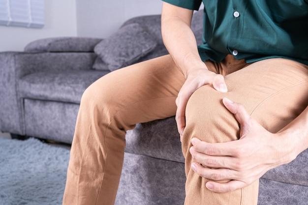 Mano de hombre sosteniendo la rodilla en el dolor mientras está sentado en el sofá.
