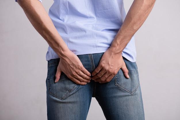 Mano del hombre sosteniendo su trasero porque tiene dolor abdominal y hemorroides