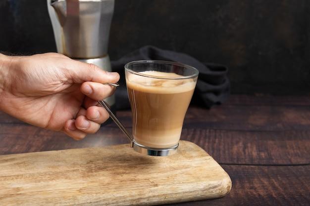 Mano del hombre sosteniendo una taza de café con leche en la mesa de madera y cafetera italiana en el fondo
