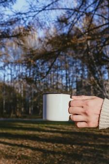 La mano del hombre sosteniendo la taza de esmalte blanco con bebida caliente al aire libre, enfoque selectivo