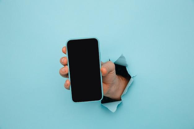 Mano de hombre sosteniendo el teléfono de papel rasgado azul.