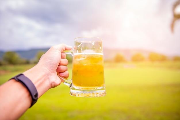 Una mano de hombre está sosteniendo un vaso de cerveza al aire libre