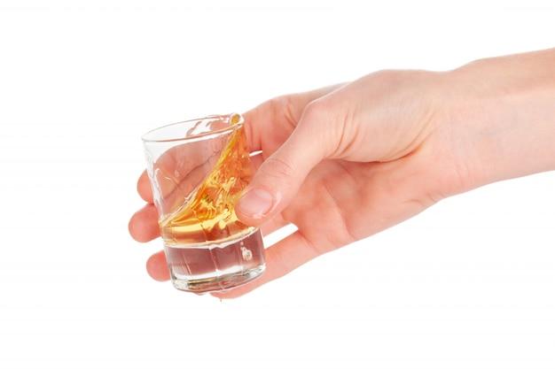 La mano del hombre sosteniendo un vaso con tequila