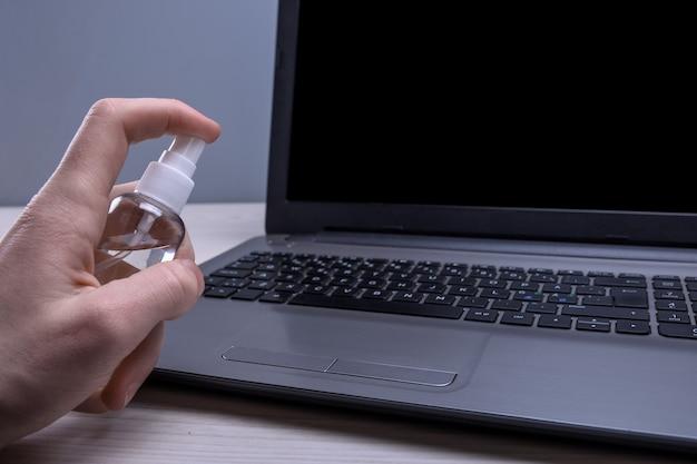 La mano de un hombre sostiene y coloca un aerosol desinfectante y desinfecta la computadora portátil