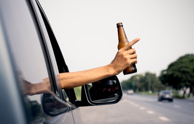 La mano de un hombre sostiene una jarra de alcohol.