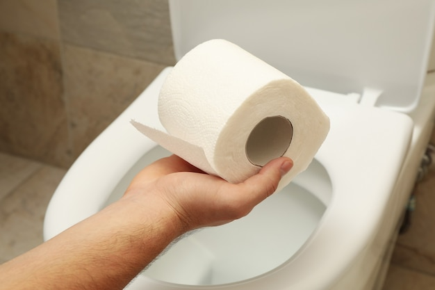 Mano de hombre sostiene papel higiénico en la taza del inodoro