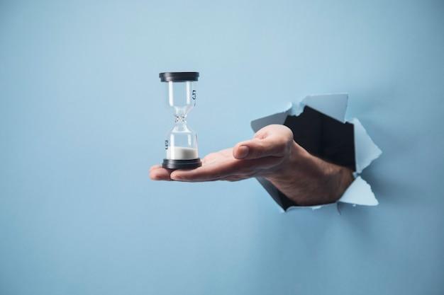 La mano del hombre sostiene un reloj de arena en una escena azul