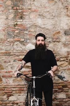 Mano del hombre con tatuaje en el asiento de la bicicleta contra la pared erosionada.
