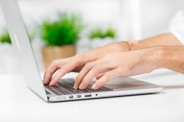 Mano del hombre en el teclado del ordenador portátil con monitor de pantalla en blanco de cerca