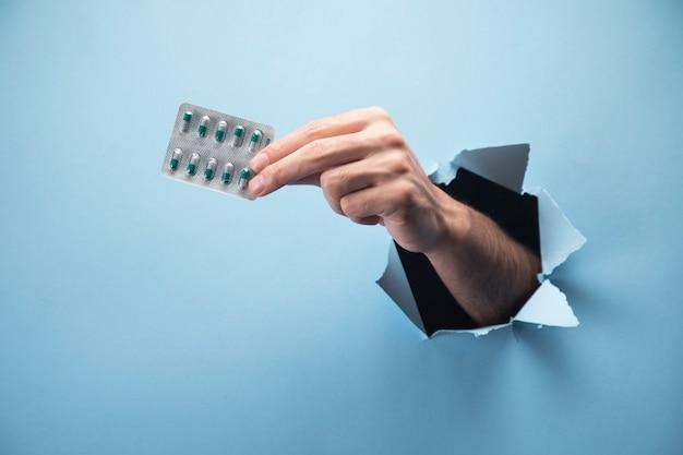 La mano del hombre tiene pastillas en la escena azul
