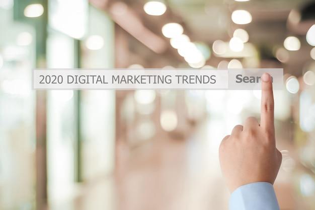 Mano del hombre tocando la estrategia comercial de tendencia de marketing digital 2020 en la barra de búsqueda sobre la oficina de desenfoque
